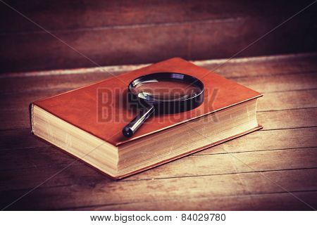 Loupa And Book On Wooden Table
