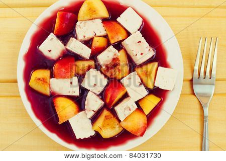 cheese and peaches in red wine sauce, dessert on wooden table