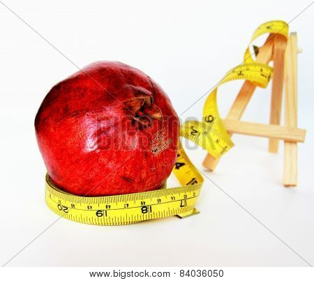 Weight Loss .Measuring tape wrapped around  tasteful fruit garnet