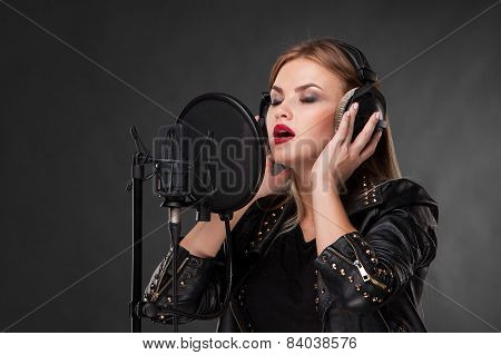 Portrait Of A Beautiful Woman Singing Into Microphone With Headphones In Studio On Black Background