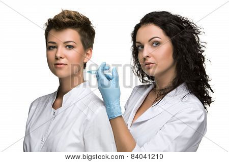 Doctor giving an injection to female patient