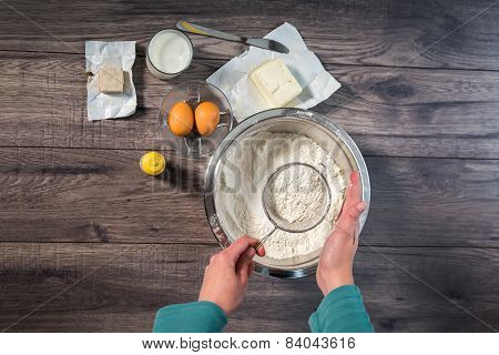 Sifting flour in the vessel. Preparing pasta. Wooden background