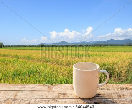 White Coffee Cup On Wooden Table With Green Paddy Rice Background