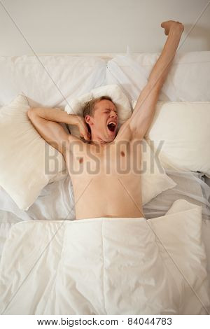 Man Waking Up And Yawning In Bed