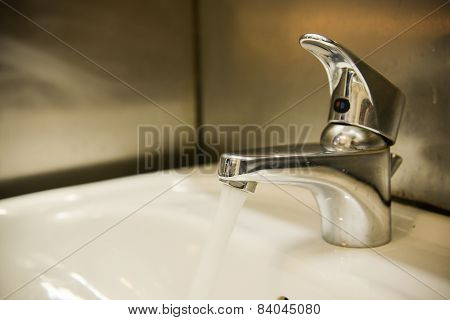 Water flow from faucet in restroom. Restroom equipment.