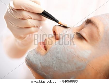 Green mask, woman in spa salon