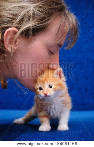 The Girl Kisses A Red Kitten