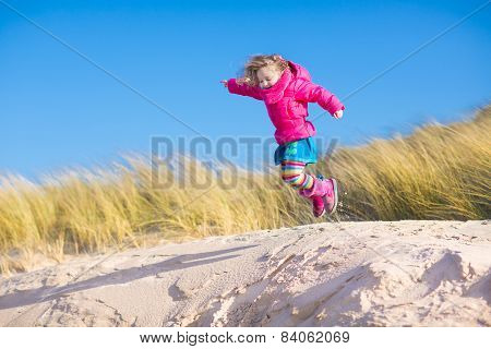 Little Girl Jumping In Sand Dunes