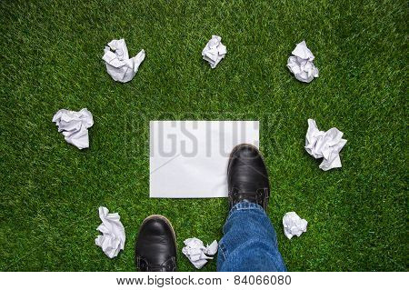 Boots On Sheet Of Paper With Cramled Sheets On The Grass