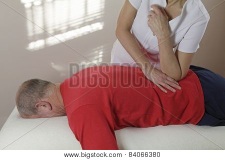 Applying pressure with elbow into lower back