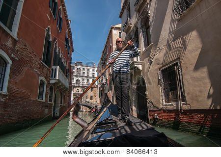 Gondolier Rides Gondola On Venetian Canal, Venice, Italy