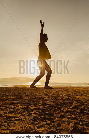 Teenage Girl  Balancing On Slackline Silhouette On The Beach