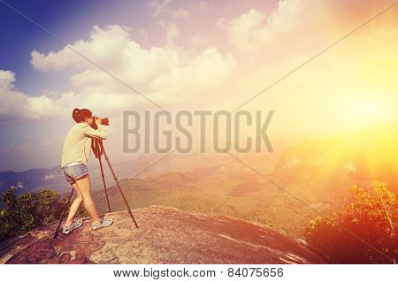 young woman photographer taking photo on sunset mountain peak