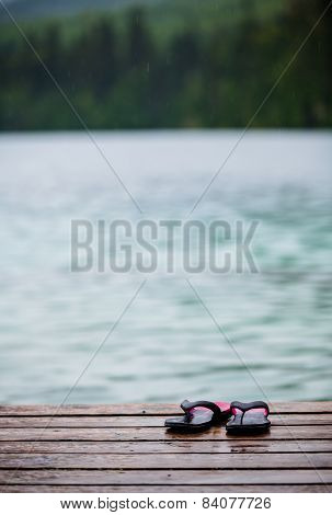 Flip Flops On A Dock In Front Of A Turquoise Water Lake
