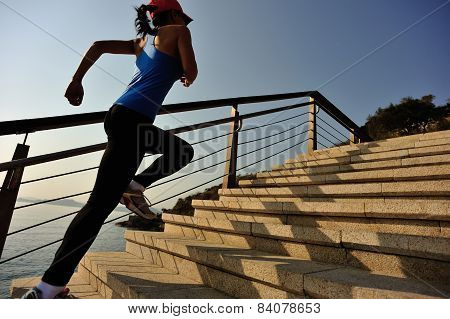 oung woman runner running up on stone stairs sunrise seaside