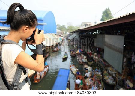 woman tourist taking photo at Damonen Saduak floating market