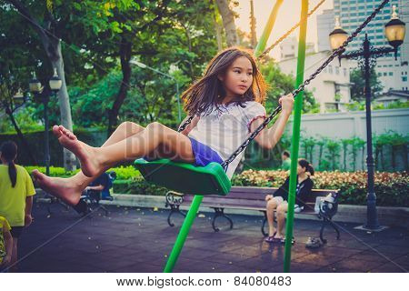 Children Welfare. Cute Thai Girl Playing A Swing