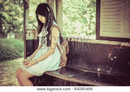 Cute Asian Thai Girl In Vintage Clothes Is Waiting Alone In An Old Bus Stop In Old Vintage Style