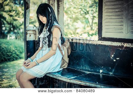 Cute Asian Thai Girl In Vintage Clothes Is Waiting Alone In An Old Bus Stop In Vintage Color Tone