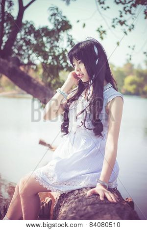 A Cute Asian Thai Girl Is Sitting On A Tree Trunk On The Riverside With Soft Breeze Blowing