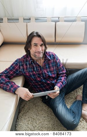 Man sitting in sofa using electronic tablet