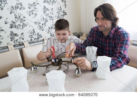father and son are repairing a chandelier