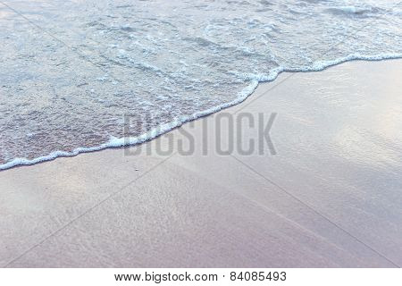 Sandy beach and waves at sunrise on a sunny morning