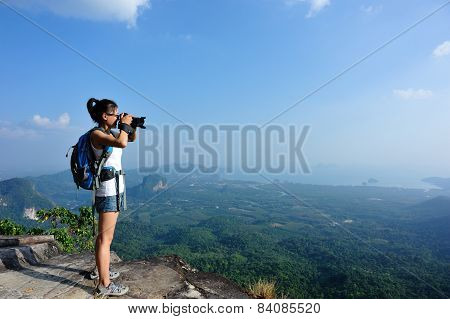 woman hiker photographer taking photto at mountain peak cliff