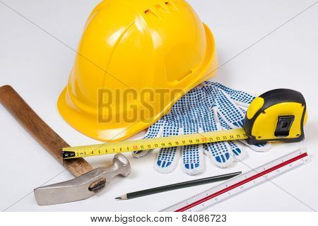 Builder's Work Tools And Yellow Helmet Over White