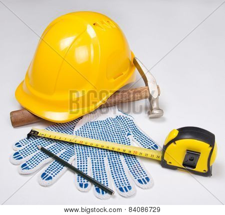 Builder's Tools - Yellow Helmet, Work Gloves, Hammer, Pen And Measure Tape Over White