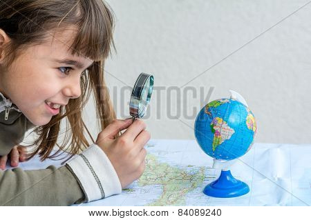 Concentrated Seven Year Old Girl Examining Globe With A Magnifying Glass