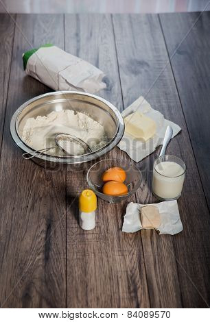 Baking cake in rural kitchen - ingredients (eggs, flour, milk, butter,ferment, salt)