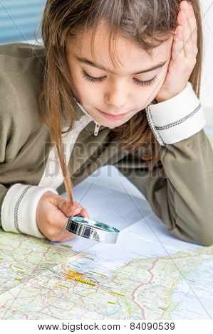Concentrated Seven Year Old Girl Examining The Map With Magnifying Glass