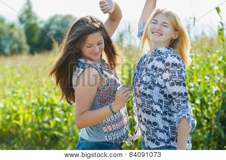 Blonde And Brunette Girls Dancing In Farm Field