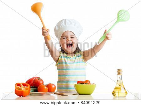 smiling little girl in cook hat with skimmer and ladle