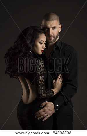 Couple Man And Woman In Love, Fashion Beauty Portrait Of Models Embracing Over Black Background