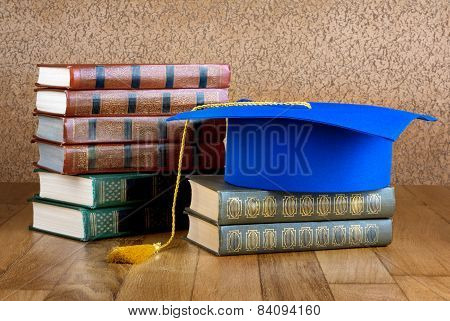 Graduation Mortarboard On Top Of Stack Of Books On Wooden Background Of Wall