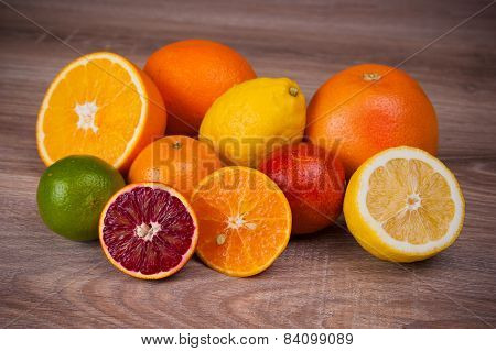 Different Citrus Fruits On Wooden Background