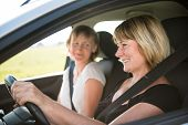picture of senior adult  - Smiling senior woman driving car with her adult child - JPG