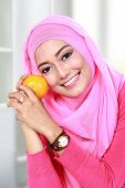 image of muslimah  - portrait of beautiful young muslim woman holding an orange - JPG