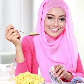 stock photo of muslimah  - close up portrait of young muslim woman eating a cereal while reading a magazine - JPG