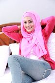 picture of muslimah  - portrait of young muslim woman relaxing body with hand behind neck on bed - JPG