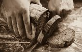 stock photo of home-made bread  - Male hands slicing home - JPG
