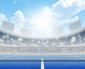 stock photo of arena  - A tennis court in an arena with a marked hard blue surface in the daytime under a blue sky - JPG