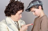 stock photo of mischief  - Woman scolding and pointing her index finger at the young boy - JPG