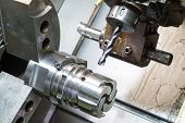 foto of machine  - operator machining die casting machine parts by high precision CNC lathe - JPG