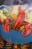 foto of steam  - Steamed lobster and vegetables in a hot steaming pot on a barbecue grill - JPG
