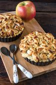 image of pie-in-face  - Selective focus on the front baked apple pie on wooden board - JPG