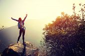 stock photo of open arms  - cheering woman hiker open arms at mountain peak - JPG