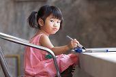 foto of kindergarten  - lovely kid practice for writing on white broad before class learning in pre kindergarten - JPG